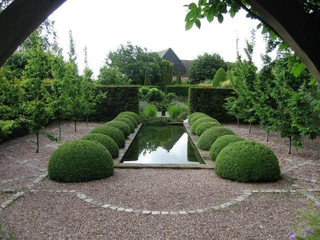 neatly trimmed hedges and a central water feature in this formal garden