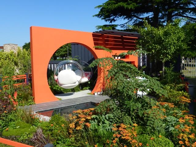 orange wall and modern seating make this garden up to date