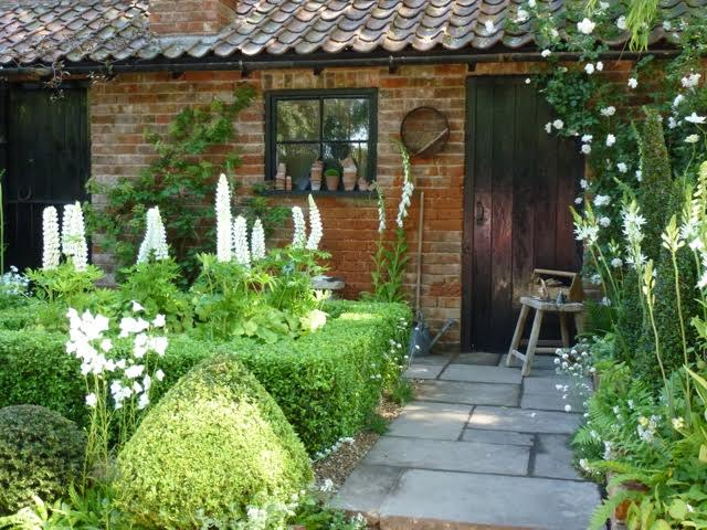 cottage garden with potts on window cills