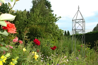obelisk plant support surrounded by flowers