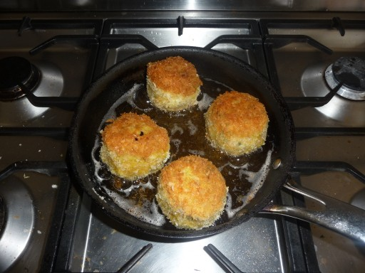 scotch eggs cooking in a frying pan