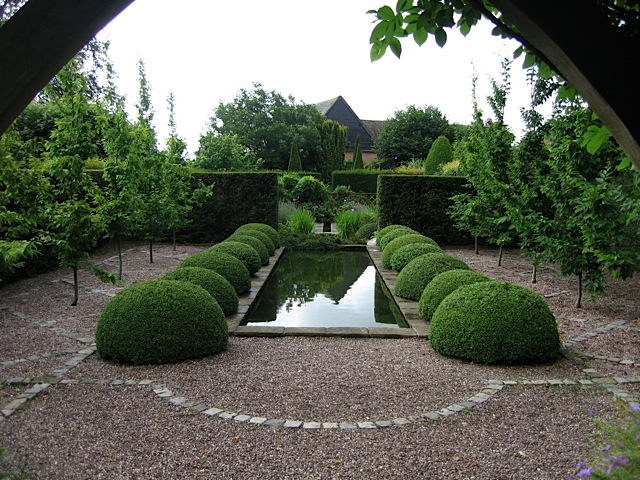 garden pond in formal garden surrounded by buxus balls