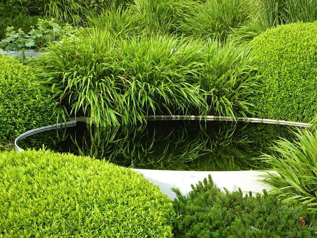 water feature surrounded by lush grass and buxus