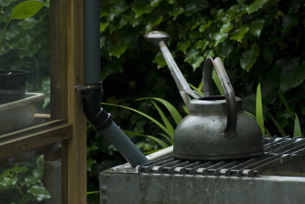 old watering can standing on rain tank