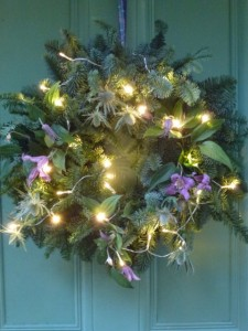 pine wreath with lights and clematis flowers