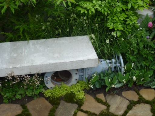 an old pipe supports a garden bench