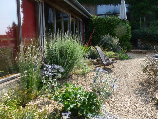 a modern gravel garden by house with full length glazing