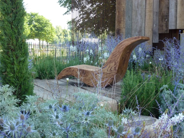 a modern chair sits in the centre of the garden
