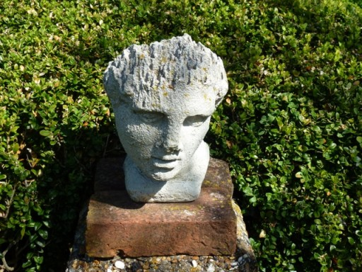 mans head on a pedestal in charleston garden