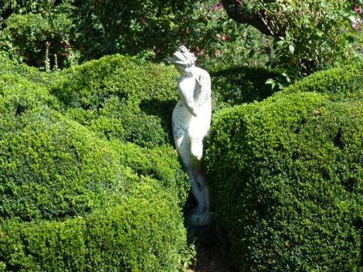 white stone statue amongst verdant green