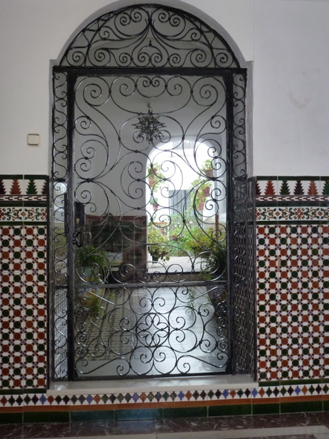 glimpse of a verdant garden through a wrought iron gate