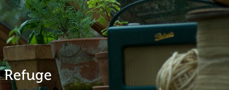 a roberts radio amongst potted plantes in a greenhouse