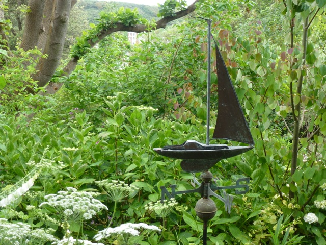 copper weathervane off ship placed among plants in the garden