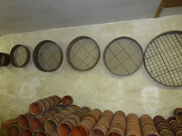 neatly stacked pots on bench with riddles on the wall above