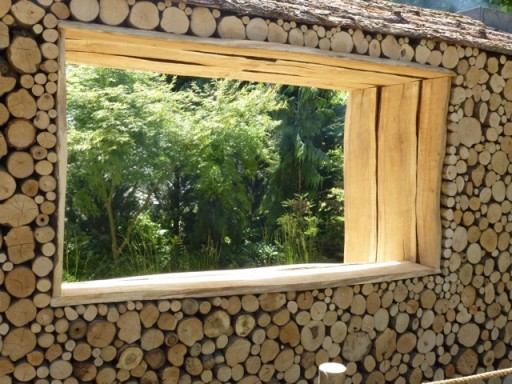 a large window breaks up a log wall